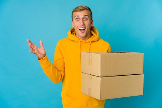 Jeune homme caucasien faisant se déplacer sur isolé recevant une agréable surprise, excité et levant les mains.