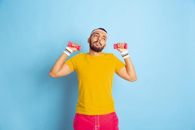 Jeune homme caucasien en formation de vêtements lumineux sur fond bleu concept de sport, émotions humaines, expression faciale, mode de vie sain, jeunesse, ventes. entraînement avec les poids colorés. copyspace.