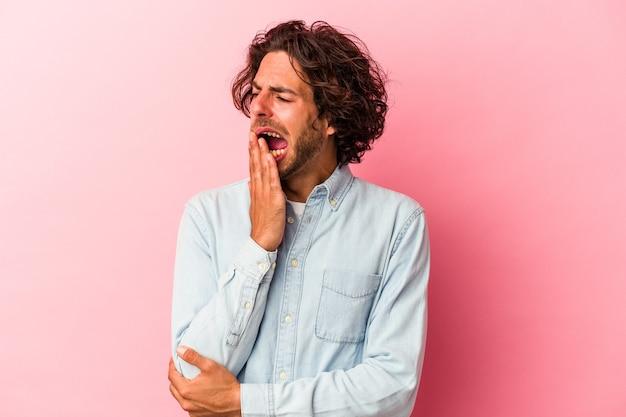 Jeune homme caucasien isolé sur bakcground rose bâillant montrant un geste fatigué couvrant la bouche avec la main.