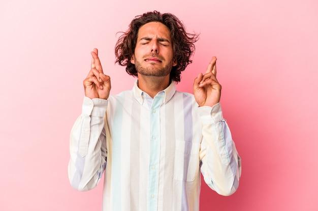 Jeune homme caucasien isolé sur bakcground rose croisant les doigts pour avoir de la chance