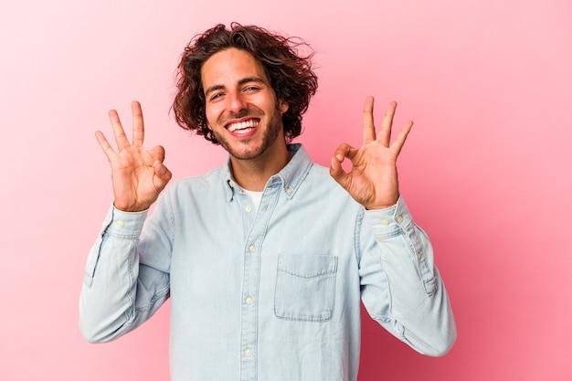 Jeune homme caucasien isolé sur bakcground rose joyeux et confiant montrant un geste correct.