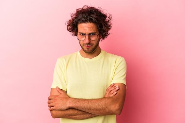 Jeune homme caucasien isolé sur bakcground rose malheureux regardant à huis clos avec une expression sarcastique.