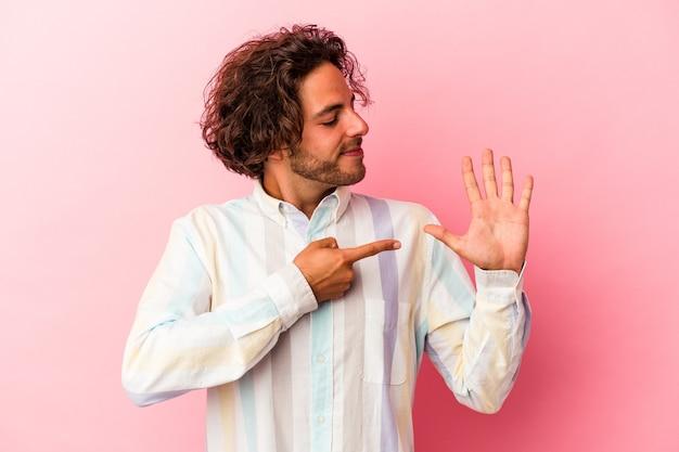 Jeune homme caucasien isolé sur bakcground rose souriant joyeux montrant le numéro cinq avec les doigts.