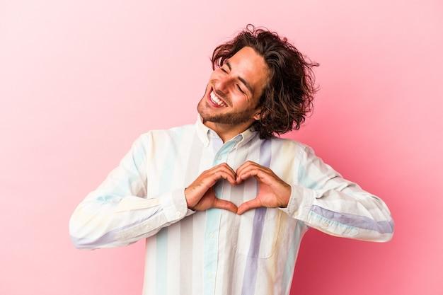 Jeune homme caucasien isolé sur bakcground rose souriant et montrant une forme de coeur avec les mains.