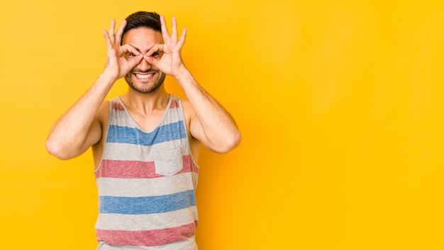 Jeune homme caucasien isolé sur bakground jaune excité en gardant le geste ok sur les yeux.