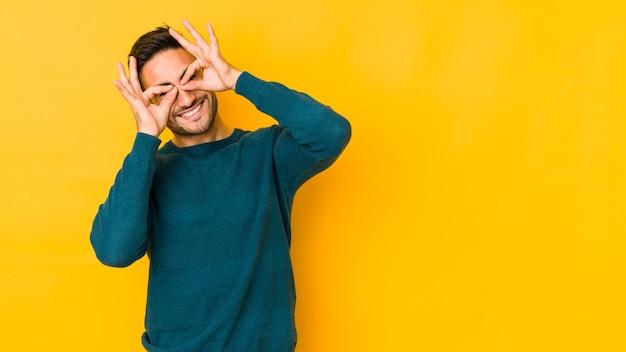 Jeune homme caucasien isolé sur bakground jaune montrant signe correct sur les yeux