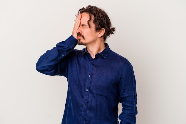 Jeune homme caucasien isolé sur blanc ayant mal à la tête, touchant l'avant du visage.