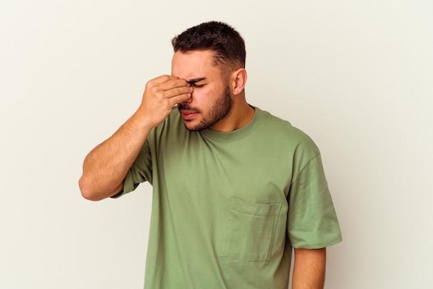 Jeune homme caucasien isolé sur blanc ayant mal à la tête, touchant le devant du visage.