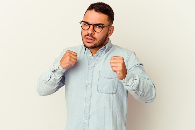 Jeune homme caucasien isolé sur blanc jetant un coup de poing, colère, combat à cause d'une dispute, boxe.