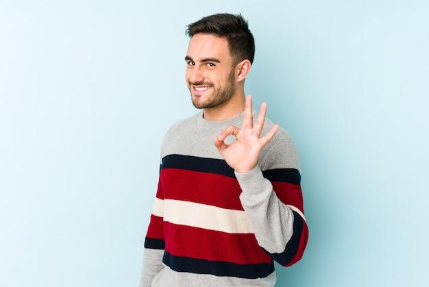 Jeune homme caucasien isolé sur bleu clignote un œil et détient un geste correct avec la main.