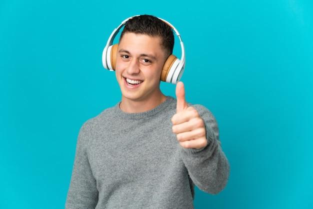 Jeune homme caucasien isolé écoute de la musique et avec le pouce vers le haut
