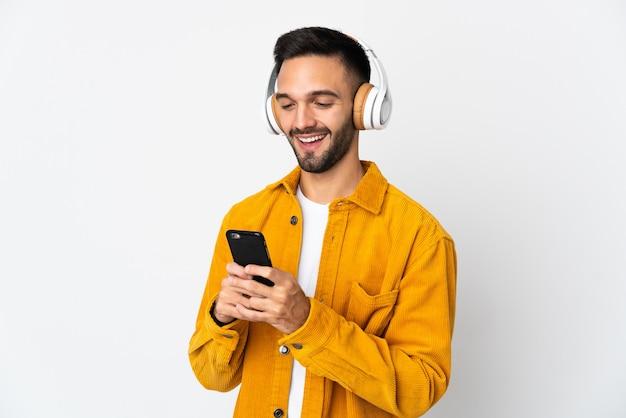 Jeune homme caucasien isolé écoute de la musique et à la recherche de mobile