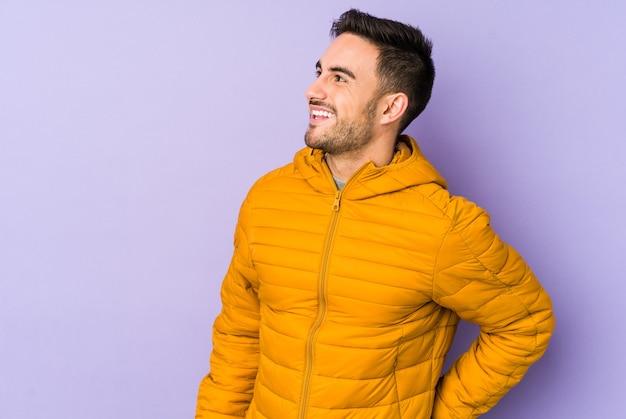 Jeune homme caucasien isolé sur l'espace violet détendu et heureux rire, cou tendu montrant les dents.