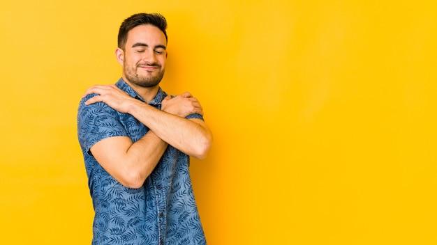 Jeune homme caucasien isolé sur des étreintes de mur jaune, souriant insouciant et heureux.
