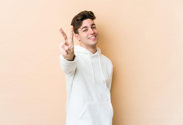Jeune homme caucasien isolé sur fond beige joyeux et insouciant montrant un symbole de paix avec les doigts.