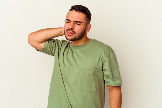 Jeune homme caucasien isolé sur fond blanc ayant une douleur au cou due au stress, en massant et en le touchant avec la main.