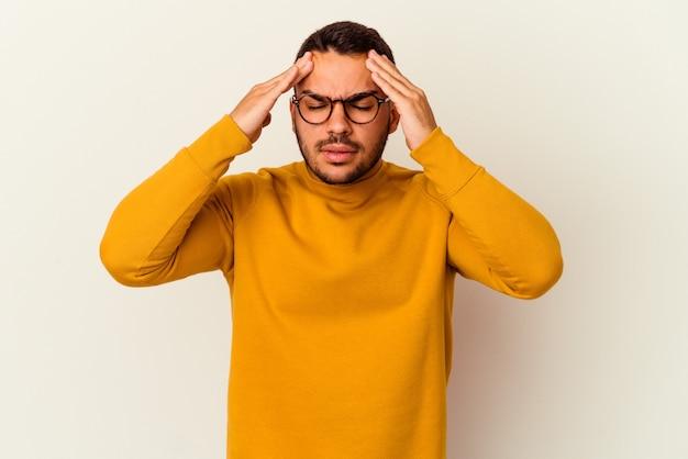 Jeune homme caucasien isolé sur fond blanc ayant mal à la tête, touchant l'avant du visage.
