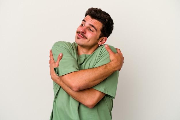 Jeune homme caucasien isolé sur fond blanc câlins, souriant insouciant et heureux.