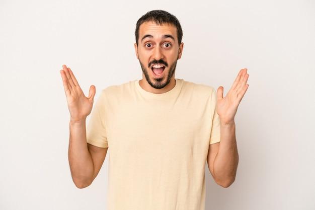 Jeune homme caucasien isolé sur fond blanc célébrant une victoire ou un succès, il est surpris et choqué.