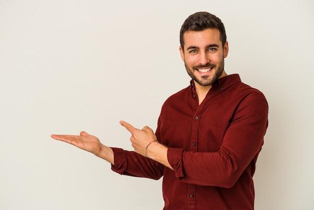 Jeune homme caucasien isolé sur fond blanc excité tenant un espace de copie sur la paume.