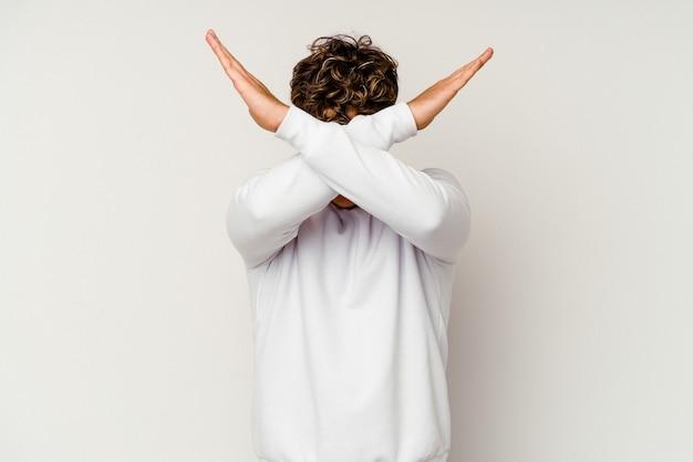 Jeune homme caucasien isolé sur fond blanc gardant deux bras croisés, concept de déni.