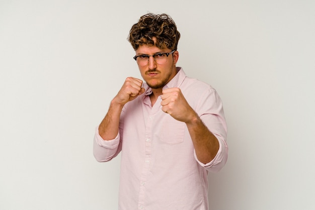 Jeune homme caucasien isolé sur fond blanc jetant un coup de poing, colère, combat à cause d'une dispute, boxe.