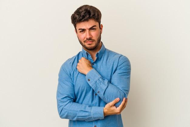 Jeune homme caucasien isolé sur fond blanc massant le coude, souffrant après un mauvais mouvement.