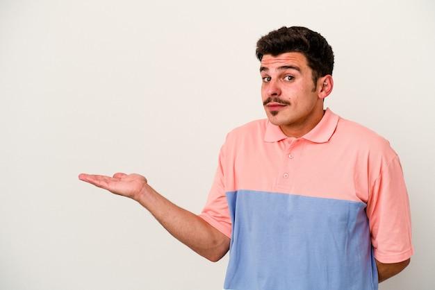 Jeune homme caucasien isolé sur fond blanc montrant un espace de copie sur une paume et tenant une autre main sur la taille.