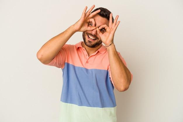 Jeune homme caucasien isolé sur fond blanc montrant un signe correct sur les yeux