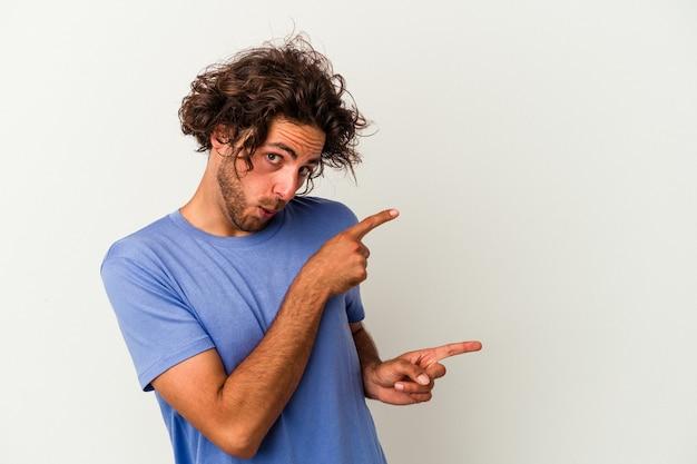 Jeune homme caucasien isolé sur fond blanc pointant avec les index vers un espace de copie, exprimant l'excitation et le désir.