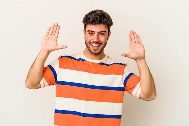 Jeune homme caucasien isolé sur fond blanc recevant une agréable surprise, excité et levant les mains.
