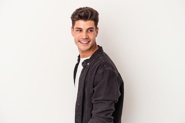 Jeune homme caucasien isolé sur fond blanc regarde de côté souriant, joyeux et agréable.