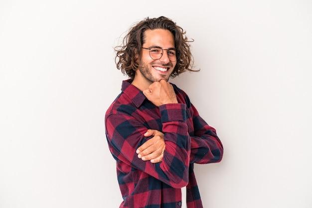 Jeune homme caucasien isolé sur fond blanc souriant heureux et confiant, touchant le menton avec la main.