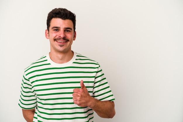 Jeune homme caucasien isolé sur fond blanc souriant et levant le pouce vers le haut