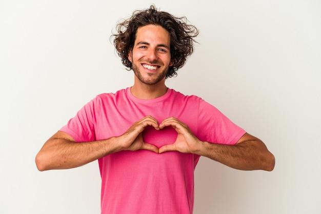 Jeune homme caucasien isolé sur fond blanc souriant et montrant une forme de coeur avec les mains.