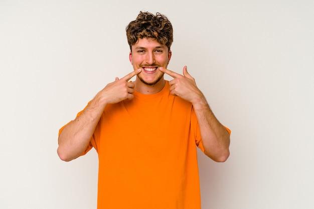 Jeune homme caucasien isolé sur fond blanc sourit, pointant du doigt la bouche.