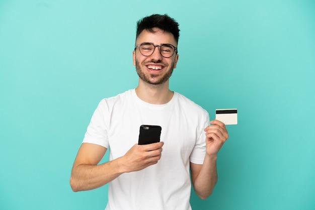 Jeune homme caucasien isolé sur fond bleu achetant avec le mobile avec une carte de crédit