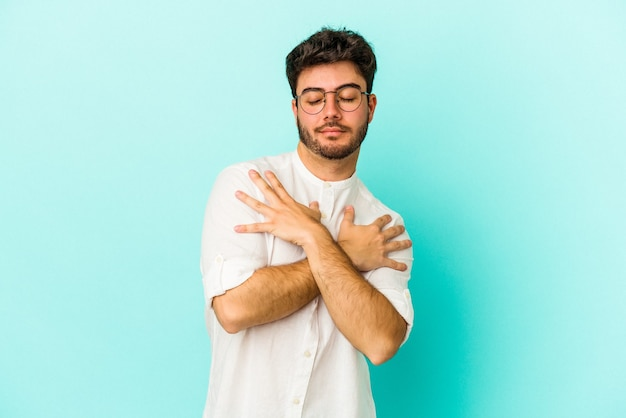 Jeune homme caucasien isolé sur fond bleu câlins, souriant insouciant et heureux.
