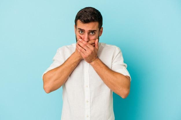 Jeune homme caucasien isolé sur fond bleu couvrant la bouche avec les mains l'air inquiet.