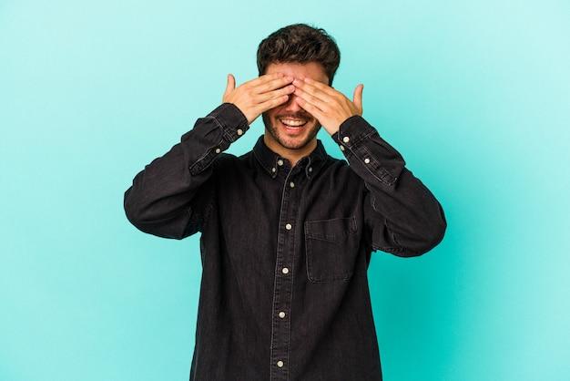 Jeune homme caucasien isolé sur fond bleu couvre les yeux avec les mains, sourit largement en attendant une surprise.