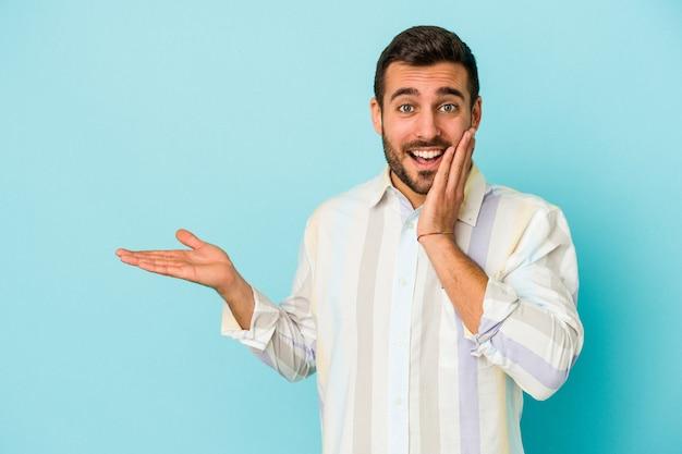 Jeune homme caucasien isolé sur fond bleu détient un espace de copie sur une paume, gardez la main sur la joue. émerveillé et ravi.