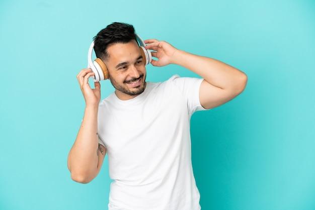 Jeune homme caucasien isolé sur fond bleu, écouter de la musique et chanter