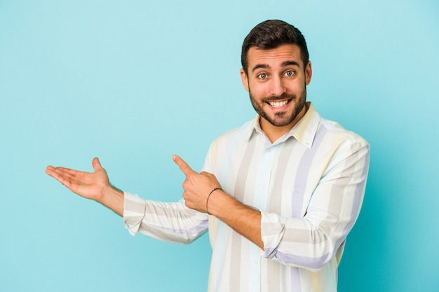 Jeune homme caucasien isolé sur fond bleu excité tenant un espace de copie sur la paume.