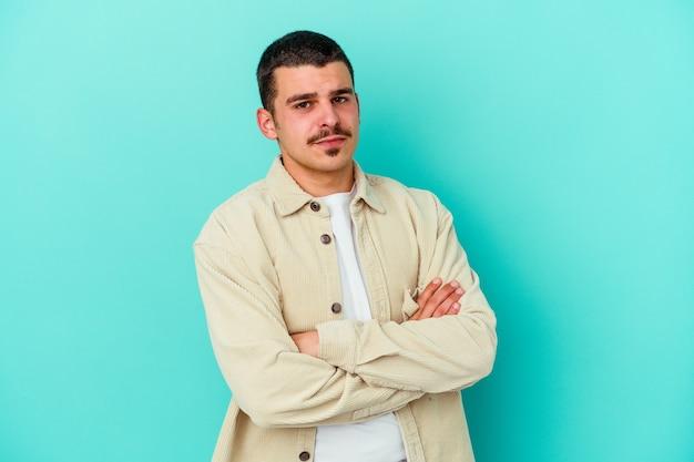 Jeune homme caucasien isolé sur fond bleu méfiant, incertain, vous examinant.