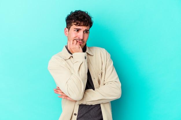 Jeune homme caucasien isolé sur fond bleu se rongeant les ongles, nerveux et très anxieux.