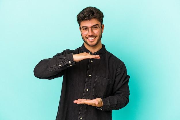 Jeune homme caucasien isolé sur fond bleu tenant quelque chose à deux mains, présentation du produit.