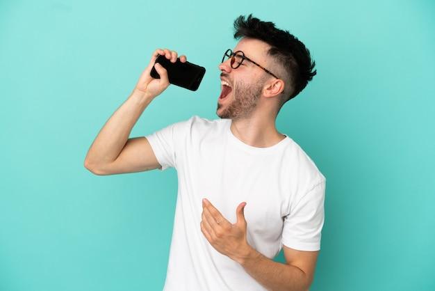 Jeune homme caucasien isolé sur fond bleu utilisant un téléphone portable et chantant