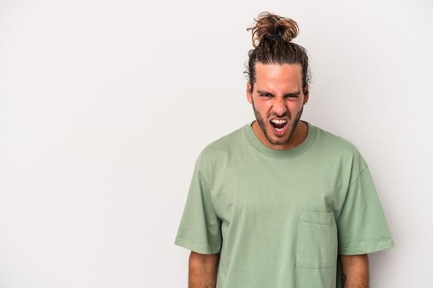 Jeune homme caucasien isolé sur fond gris criant très en colère, concept de rage, frustré.