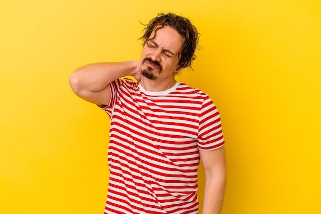 Jeune homme caucasien isolé sur fond jaune ayant une douleur au cou due au stress, en le massant et en le touchant avec la main.