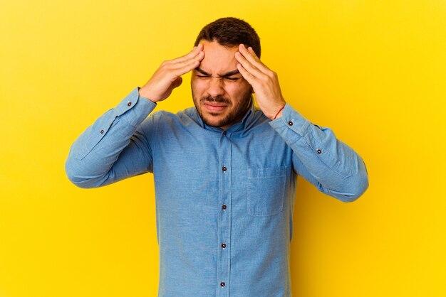 Jeune homme caucasien isolé sur fond jaune ayant mal à la tête, touchant l'avant du visage.